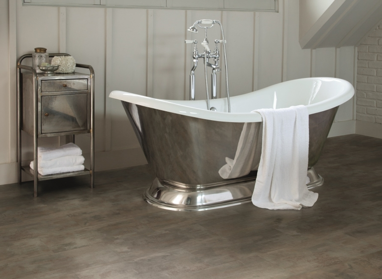 Wooden LVT flooring in a bathroom with an elegant stainless steel bath tub